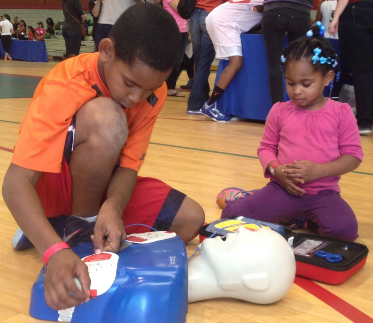 Youth learning how to use AED